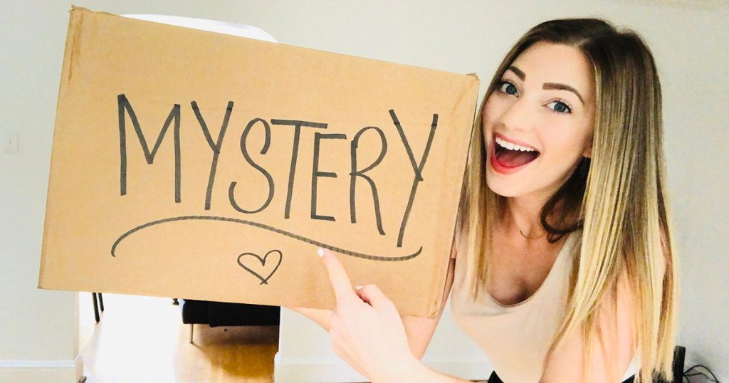 woman with blonde hair holding up a brown box that says mystery on it