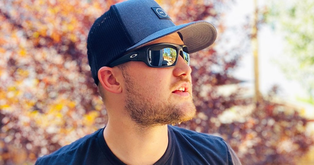 man standing outside wearing grey hat, black oakley sunglasses, and black t-shirt