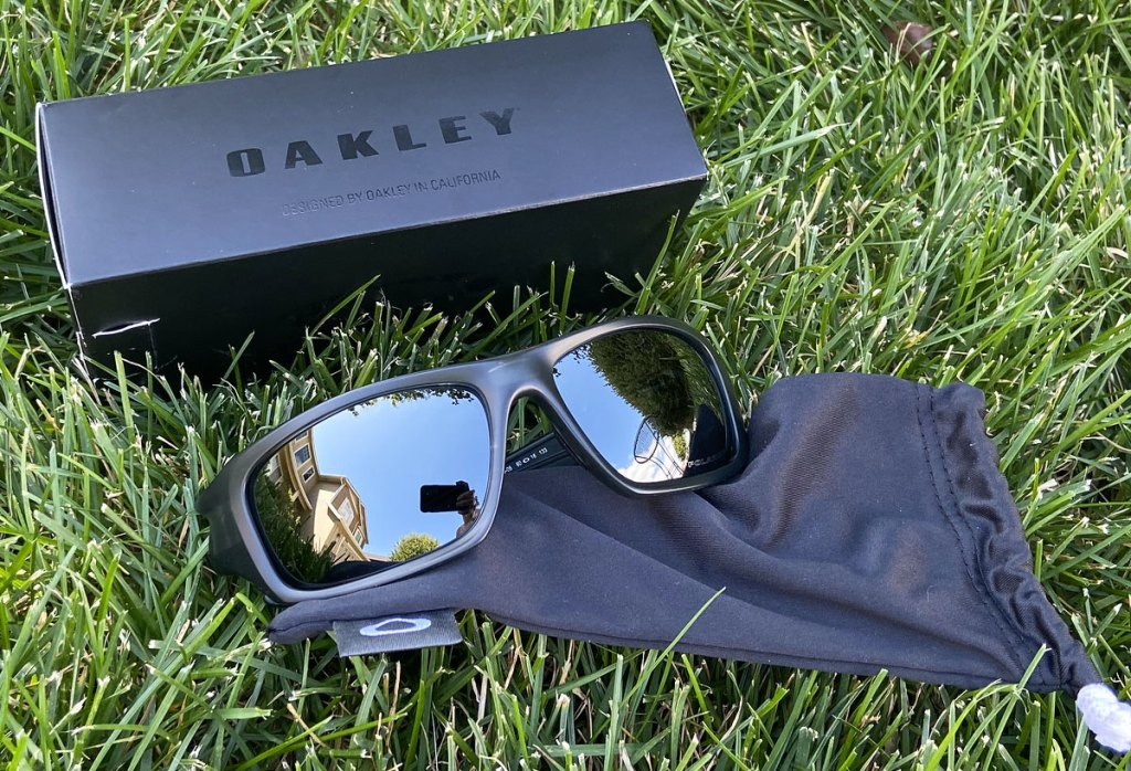 pair of black oakley sunglasses laying in grass near to storage bag and box
