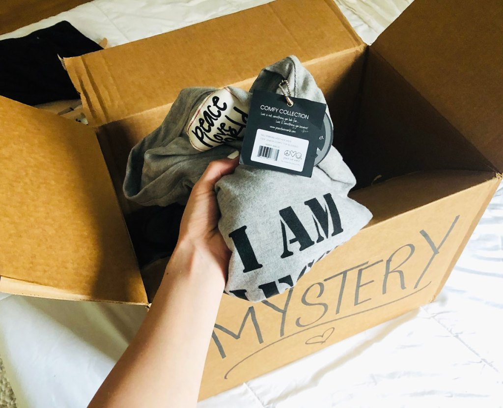 woman pulling a grey tshirt out of a brown mystery box