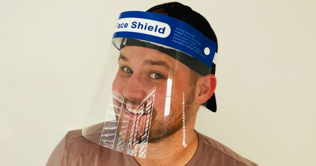 man in brown t-shirt wearing a protective face shield on his head
