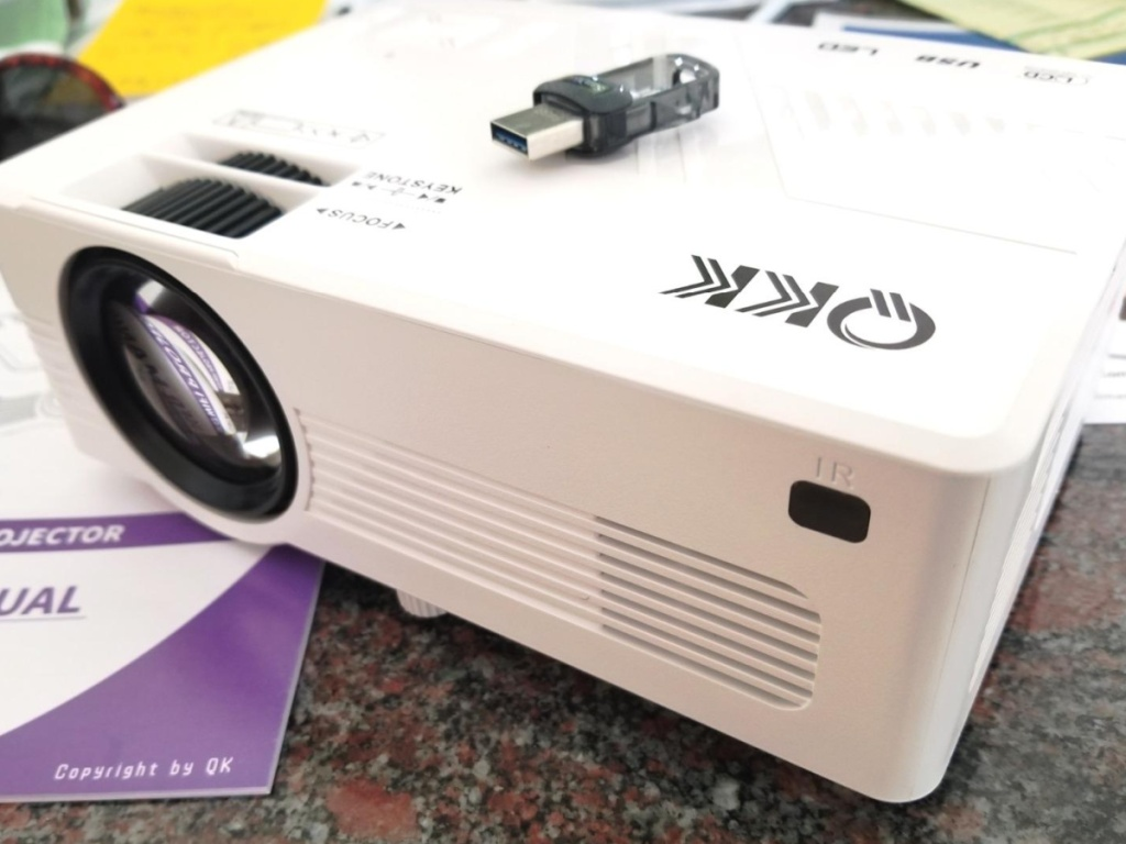 QKK small mini wifi projector sitting on a desk with a booklet and usb drive