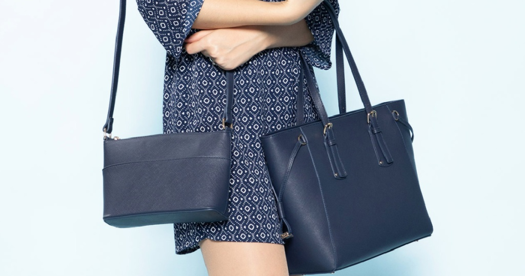 woman holding large navy tote and smaller crossbody bag