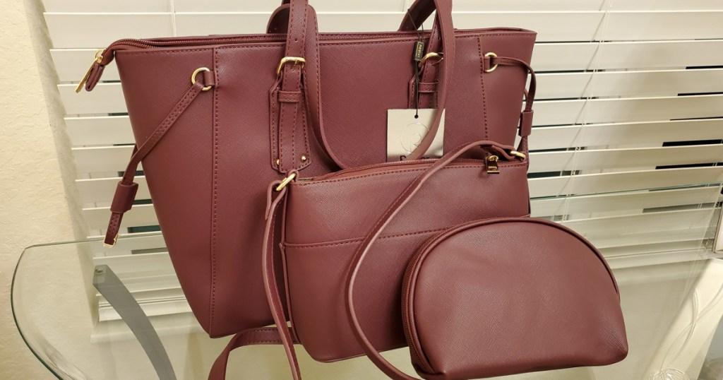 3-piece purple vegan leather purse set sitting on a glass table