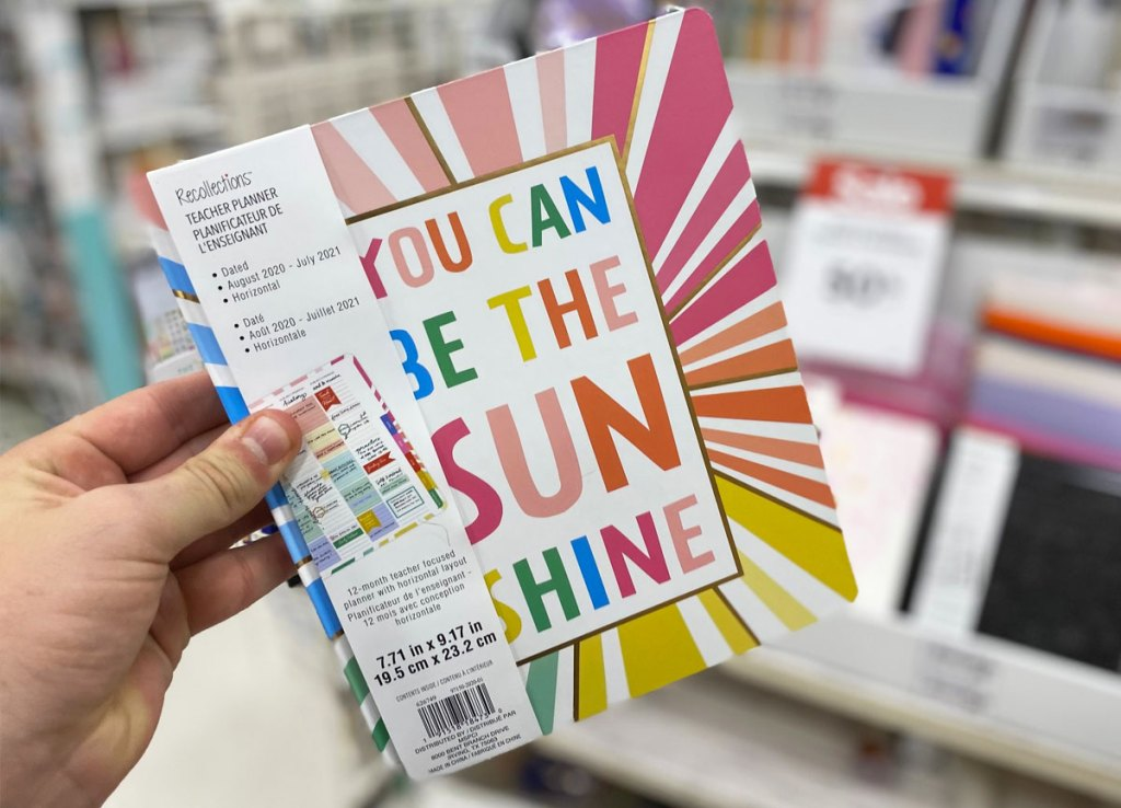 person holding up a rainbow colored planner