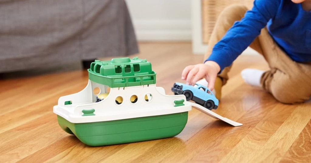 little boy playing on the floor with a green and white ferry boat