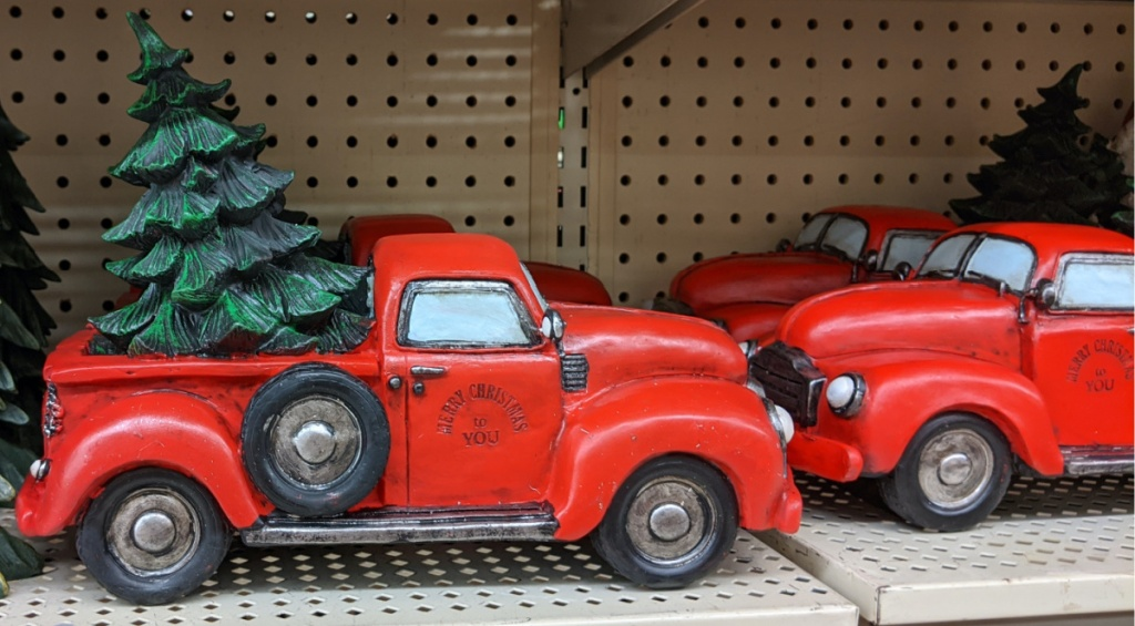 red truck with Christmas tree in bed decor on store shelf