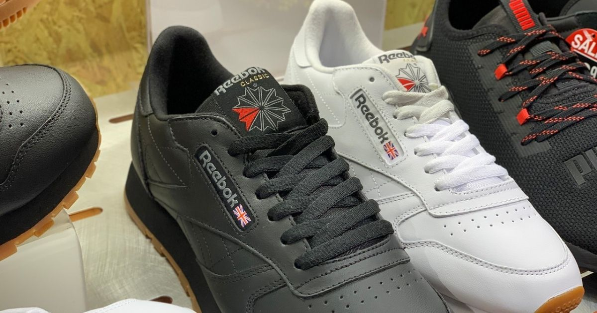 black and white pair of reebok shoes on shelf