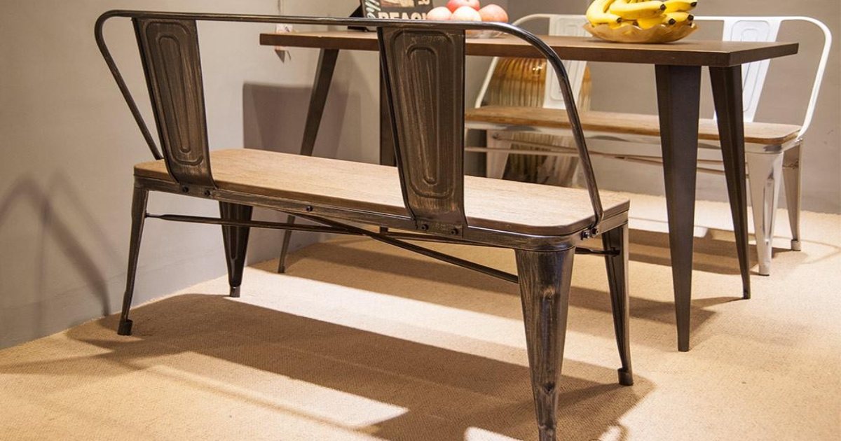 Rustic metal bench in front of a rustic table in a kitchen