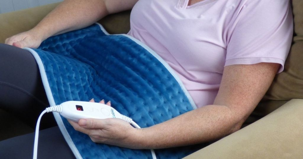 woman wearing pink shirt with blue heating pad on stomach