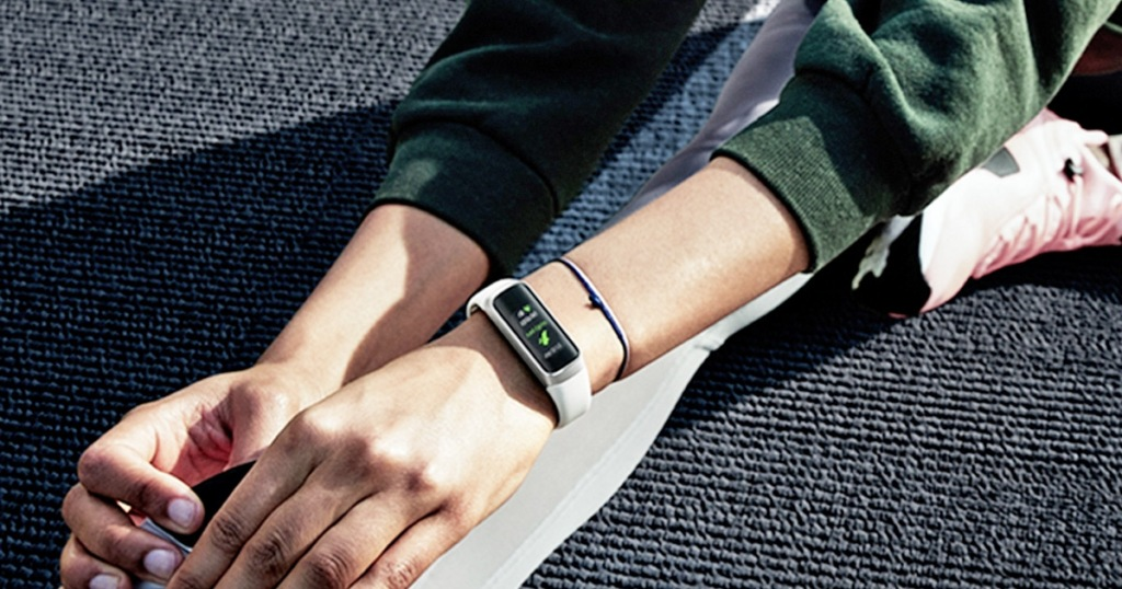 woman sitting on ground stretching and wearing a white Samsung Galaxy Fit band on her wrist
