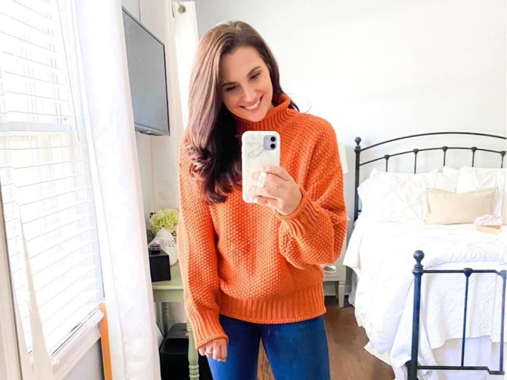 woman taking selfie in orange sweater