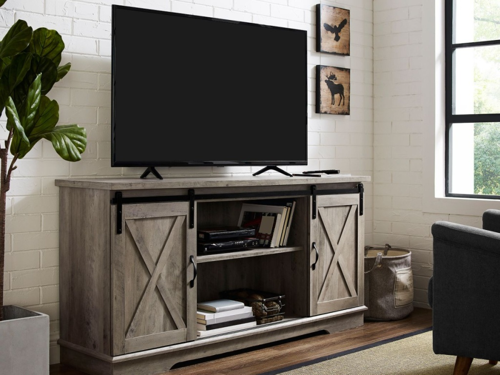 farmhouse style tv stand with gray finish and tv sitting on top