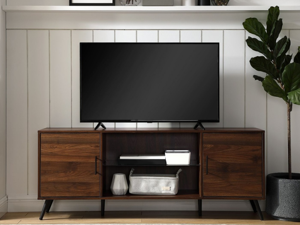 brown entertainment stand with tv placed on it