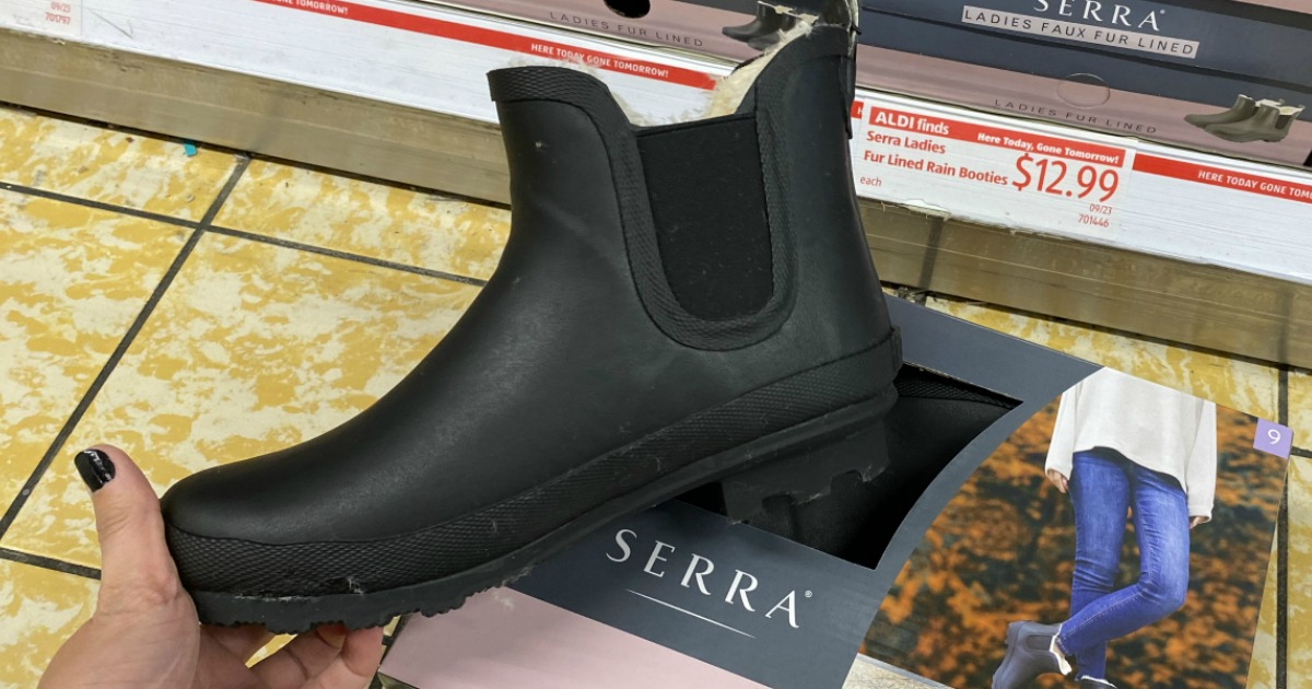 Women's rain boot in hand near box