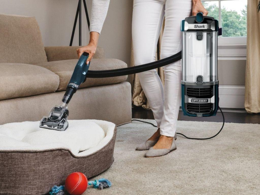 Woman using liftaway shark pet vacuum on pet bed