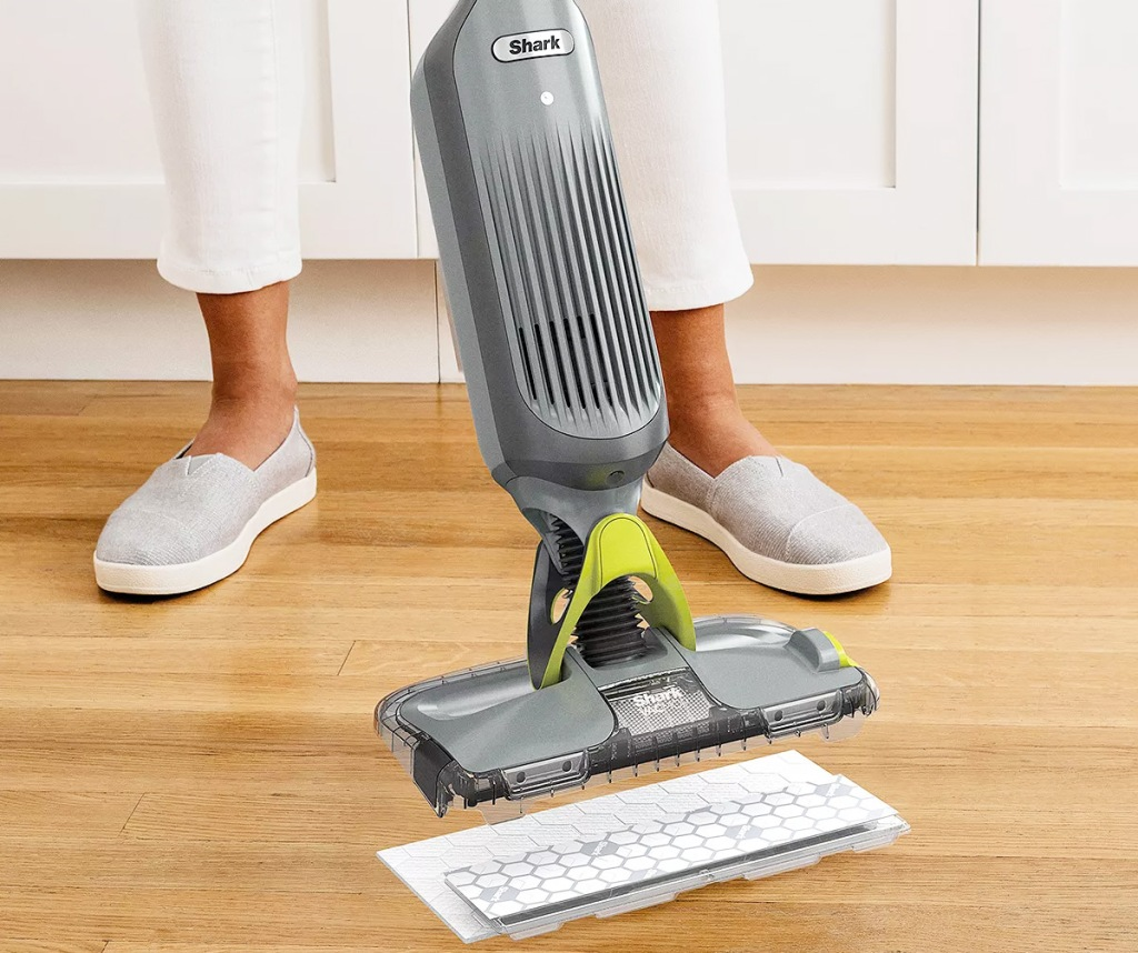 person replacing the mop pad on a shark vacmop on hardwood floor