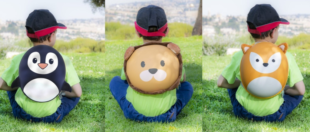 kids sitting in the grass wearing animal backpacks