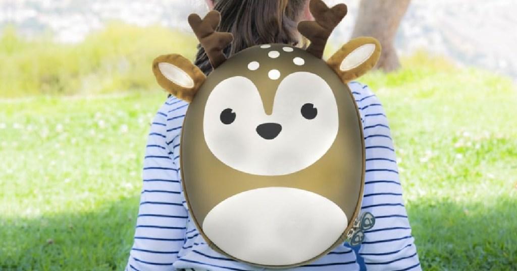 little girl sitting outside wearing a deer backpack