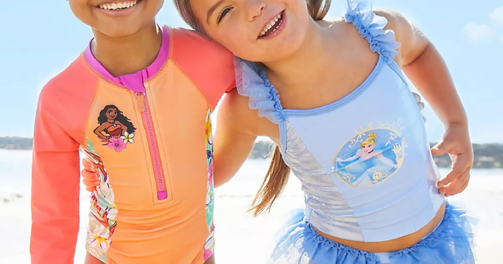 two little girls wearing bright and colorful Disney swimsuits on a beach