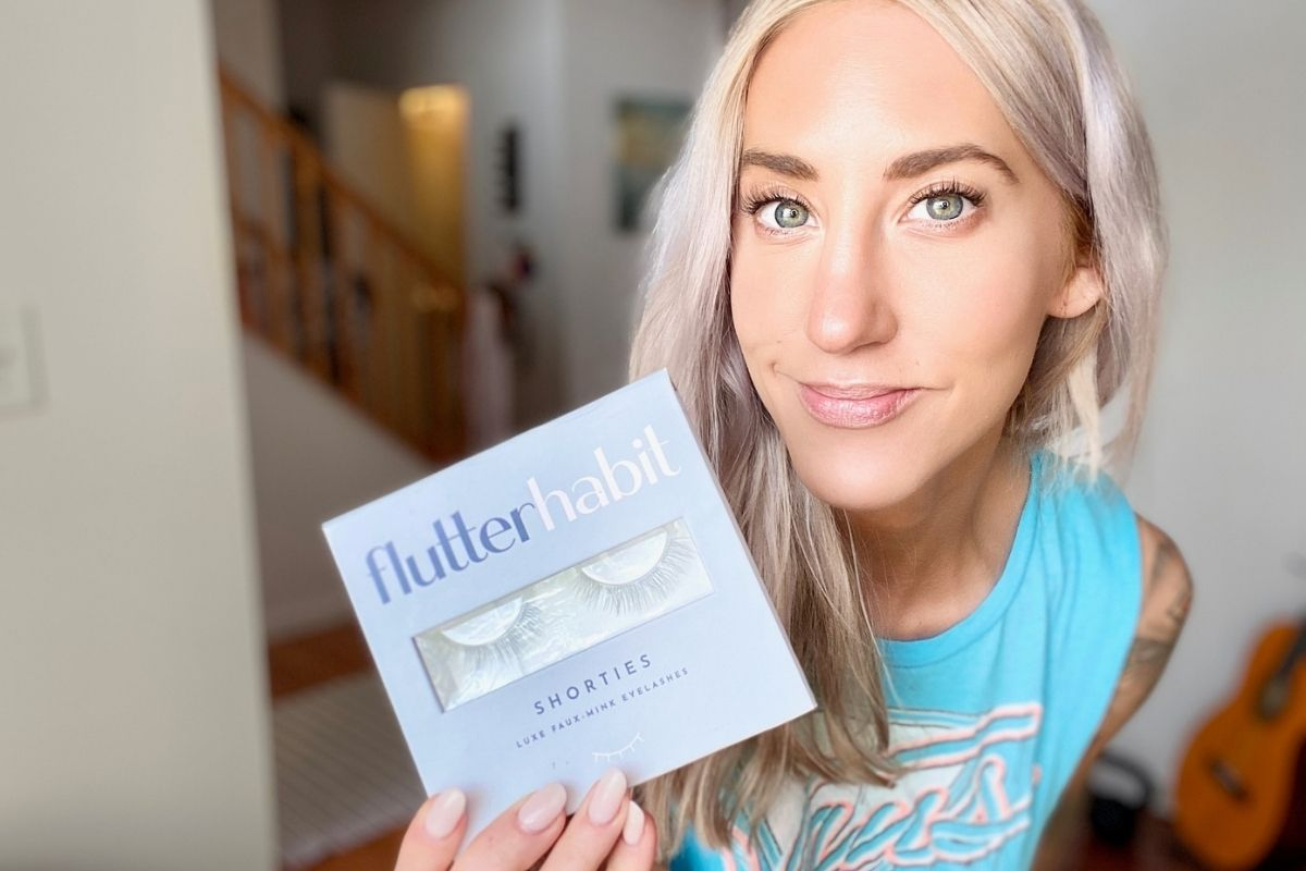 A woman holding a box of shortie eyelashes and wearing them