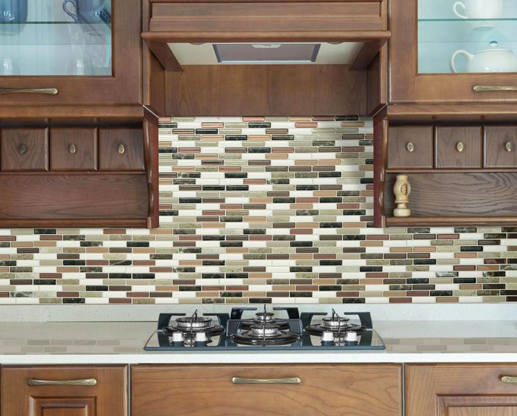 brown and cream colored peel and stick tile backsplash on wall under brown wood cabinets in front of stove