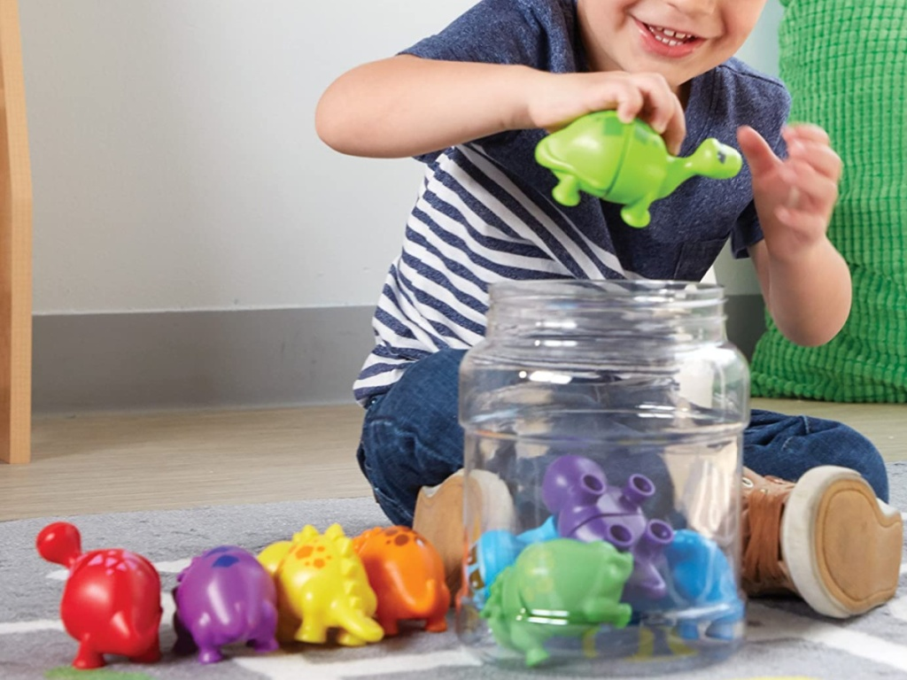 boy playing with dinosaur toys on floor