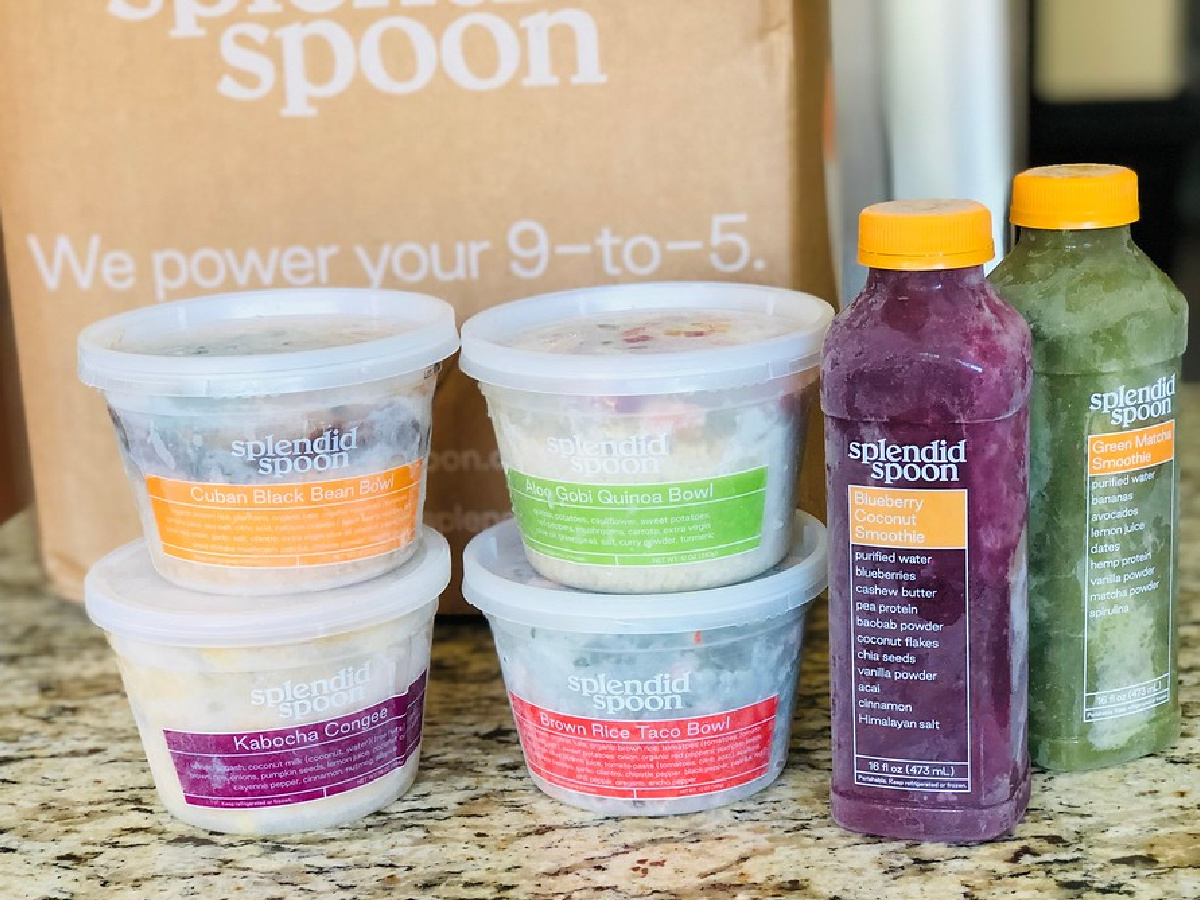 four food bowls and two smoothies next to shipping box on kitchen counter