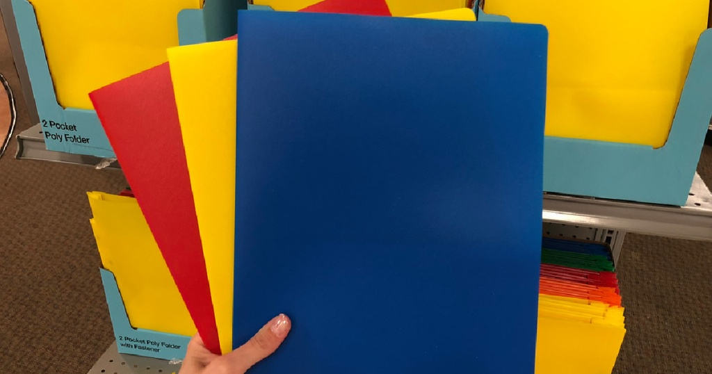 hand holding different colored folders in store