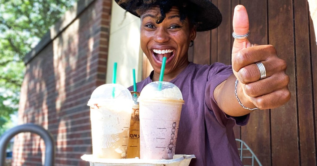 woman holding try of starbucks drinks