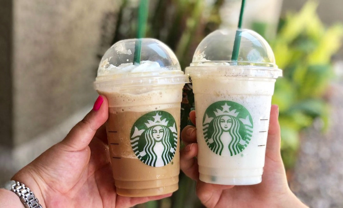 two people holding up Starbucks Frappuccinos