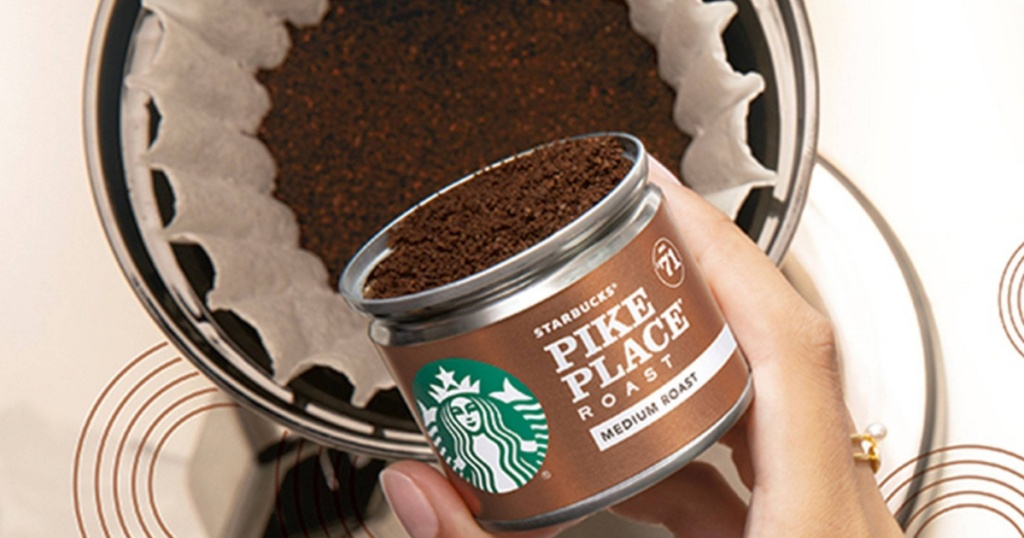 hand pouring ground coffee from small can into coffee filter