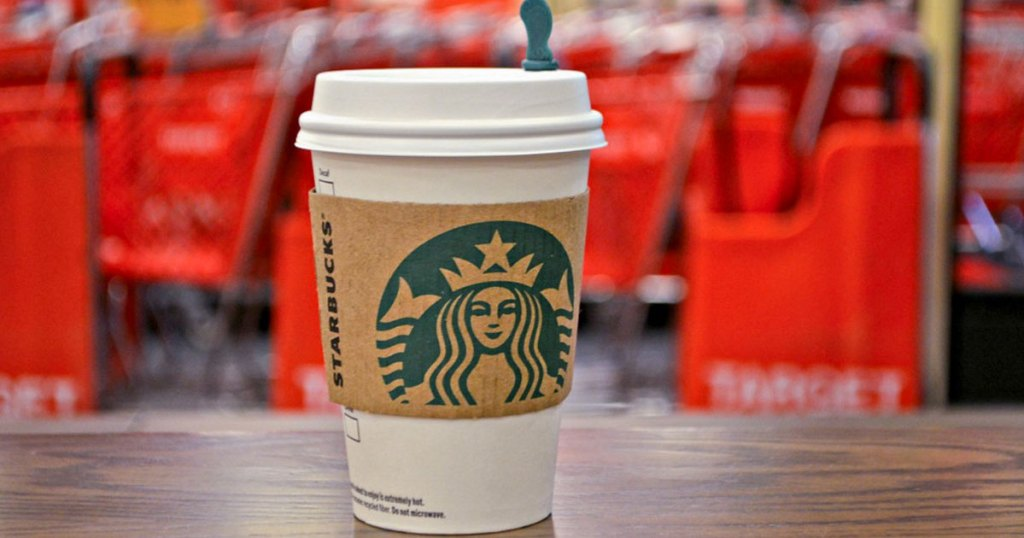 Starbucks hot drink on wood table in front of red Target shopping carts