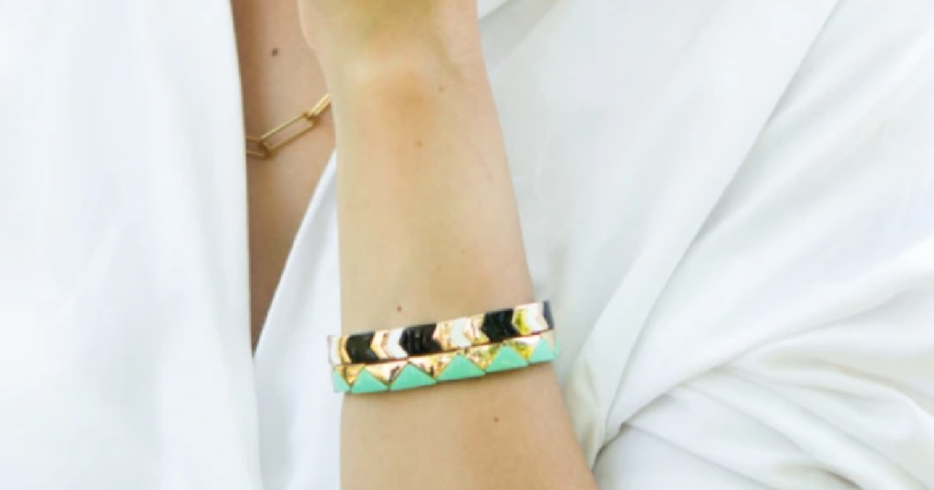 woman wearing 2 gold triangular bracelets, one black and one turquoise
