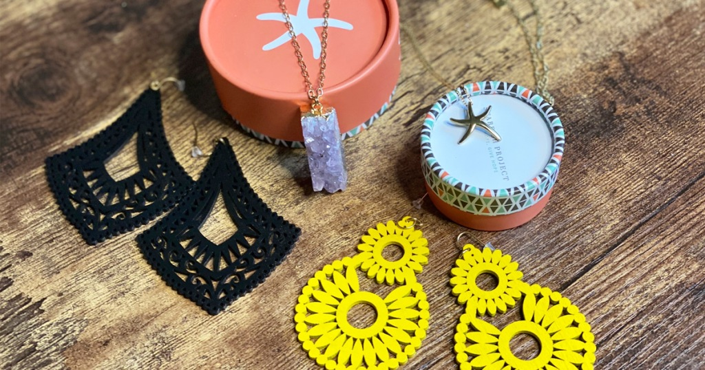 two pairs of black and yellow earrings and two necklaces on wood table with round jewelry boxes