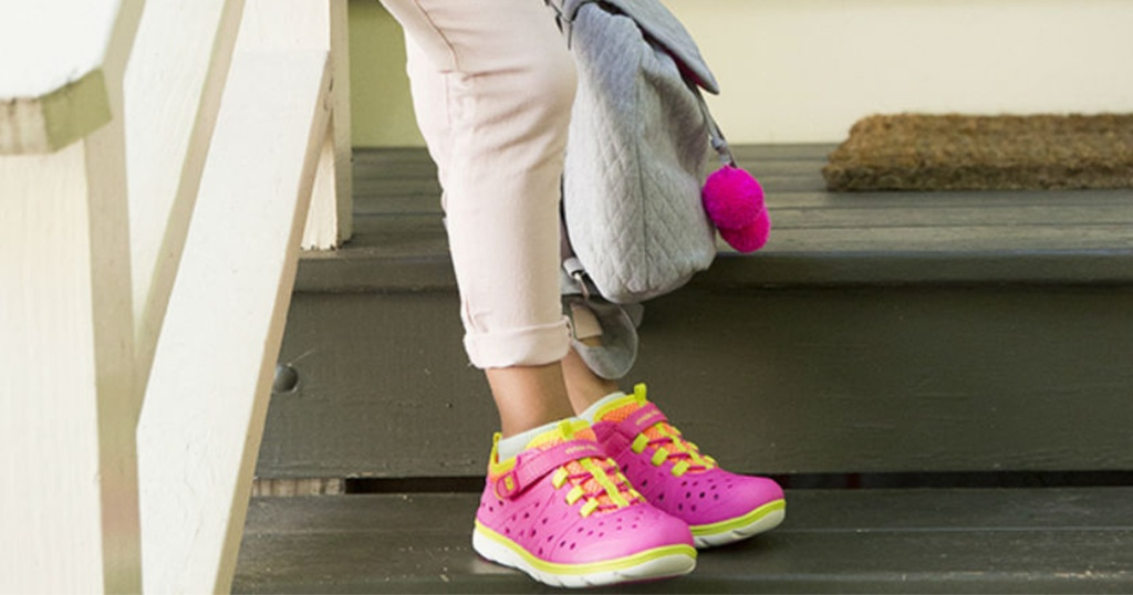 girl wearing pink and yellow sneakers on steps and grey bag