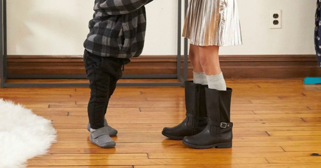 two kids standing facing each other on hardwood floor wearing boots