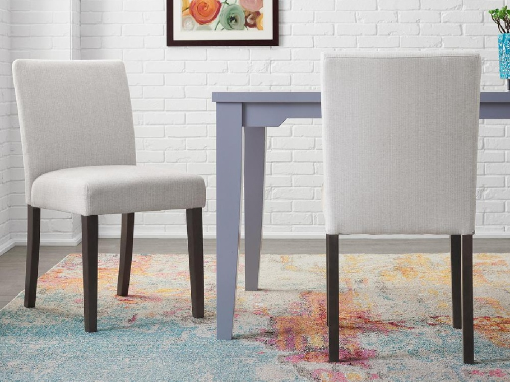 white chairs with wood legs on carpet by table