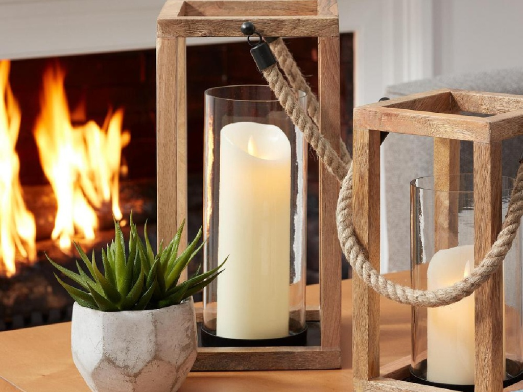 wooden lantern candle holders on table with fireplace in background