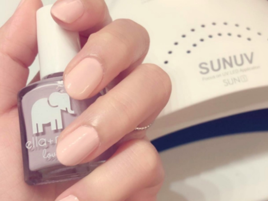 lady holding nail polish near a nail dryer