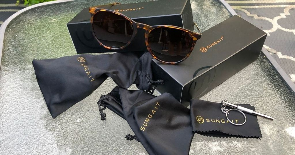 brown framed sunglasses resting on packaging with carrying bags and cleaning cloth next to packaging
