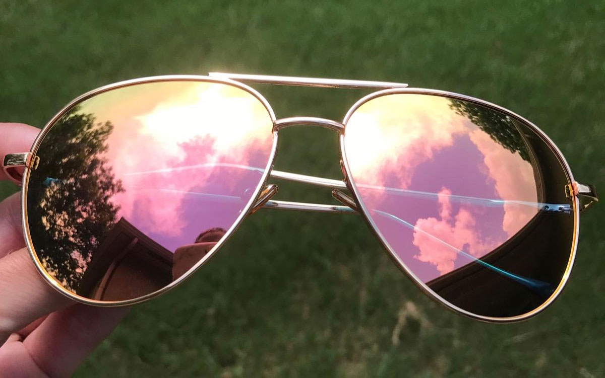 person holding pair of aviator sunglasses with gold frames and pink mirrored lenses