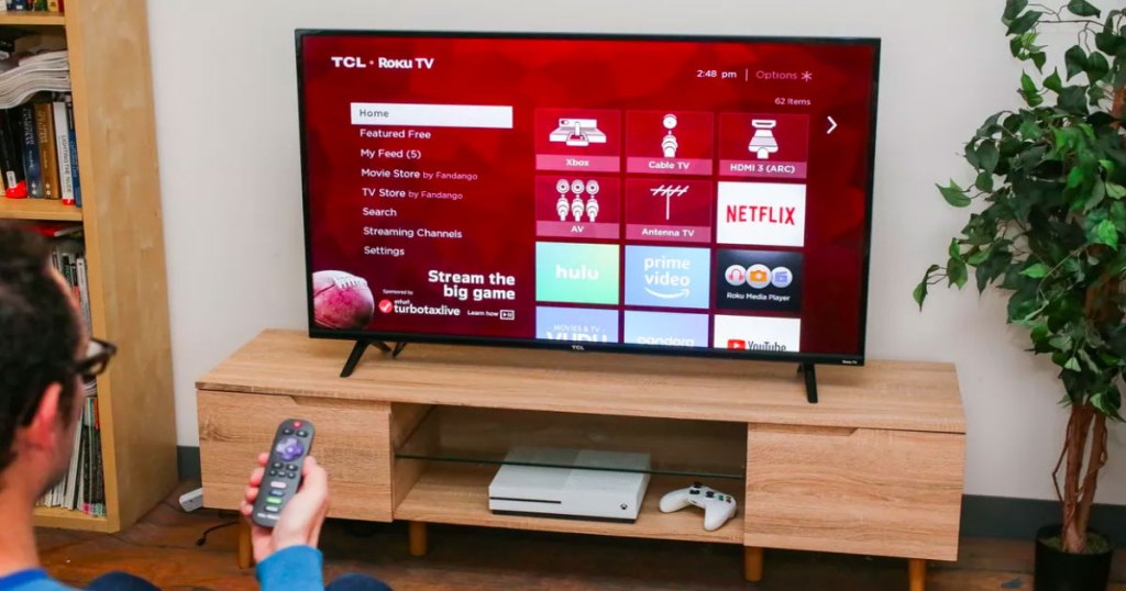 man pointing a Roku remote at a smart tv showing menu screen with apps