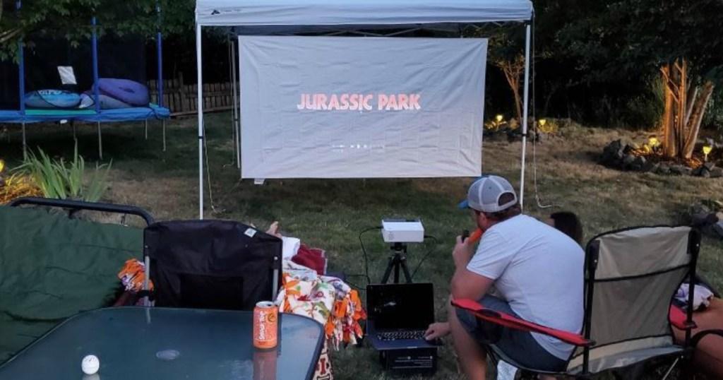 man watching Jurassic Park on projector screen