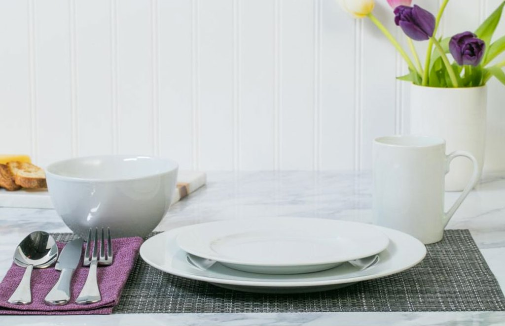 round white dinnerware set on table with silverware and vase of flowers