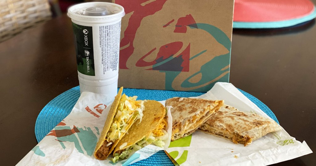 two taco bell tacos, grande stacker, and medium drink in front of taco bell box