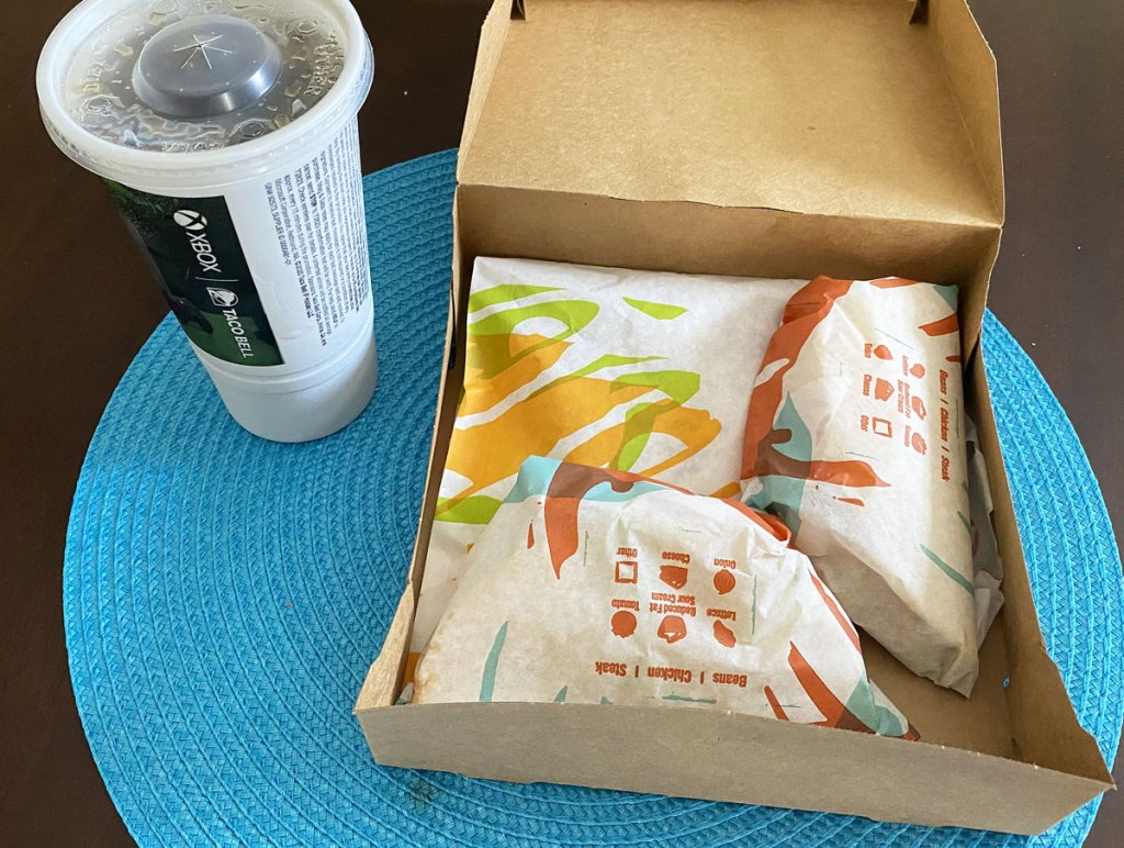 brown box with three taco bell items inside and drink cup next to it on blue placemat
