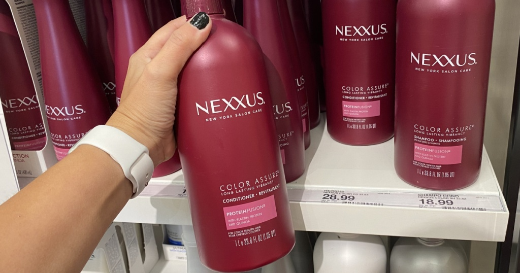 hand holding a large bottle of nexxus shampoo in store at target