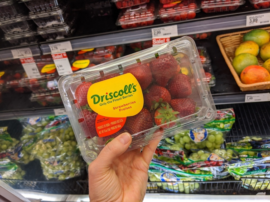 hand holding package of strawberries in the produce section at target