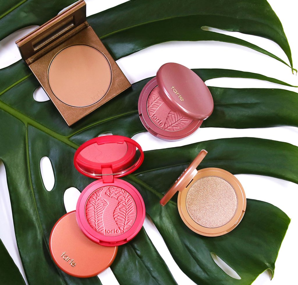 single compacts of tarte blushes and bronzers on a large green palm leaf